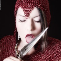 Dahlia Dark in a red chainmail coif