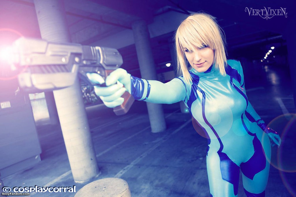 Young woman in Zero Suit Samus costume poses holding prop pistol in firing position.